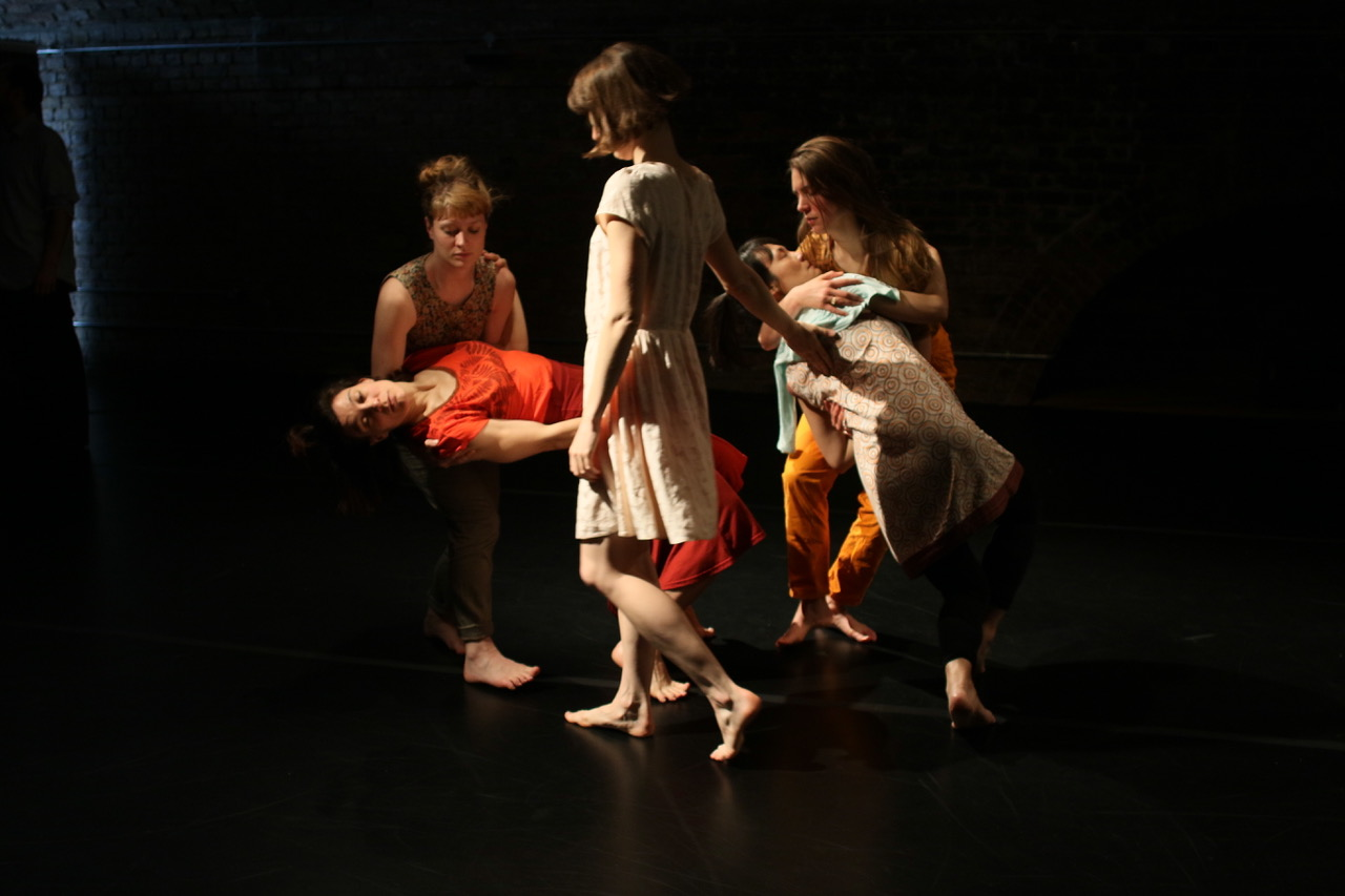 Five women in a dance piece, 2 women falling, 2 women catching, the other standing turned away from the camera.